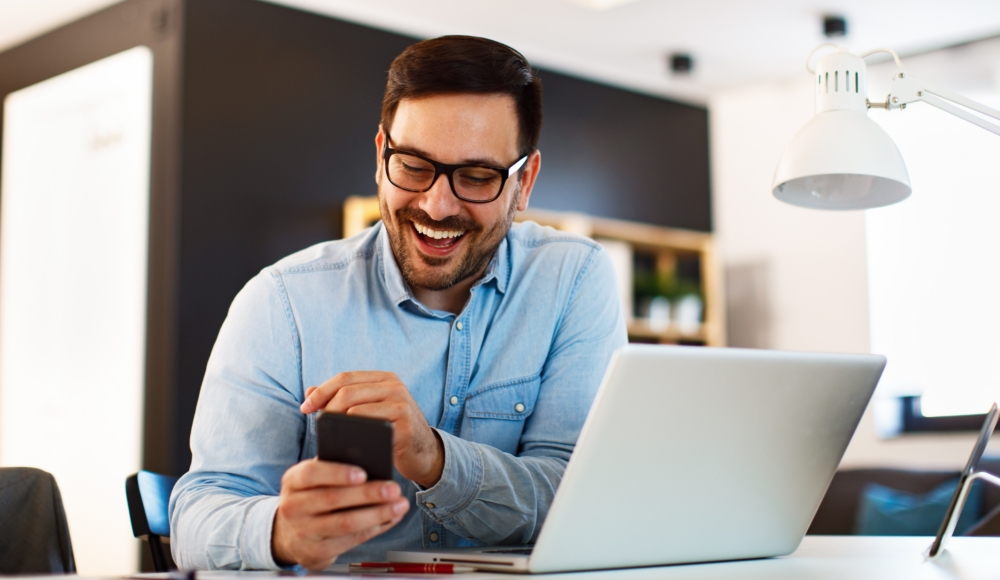 Young Business Man Working At Home With Laptop And Uses A Smartphone